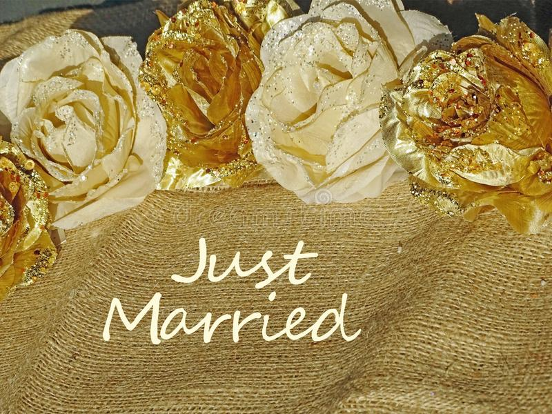 Background of golden flowers with text Just Married. Background of golden and white flowers on cotton texture with tekst Just Married royalty free stock images