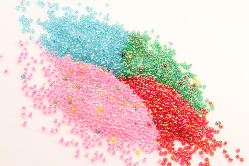 Background of granules inclined. Plastic granules united colors of four tilted view stock image