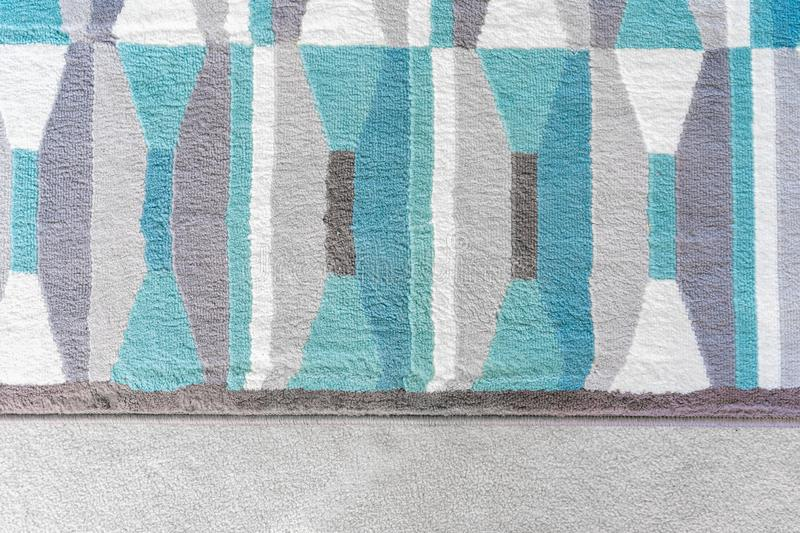 Background graphic, top view of a geometric rug with blue and grey color patterns, on top of a beige carpet, as a design element stock photo