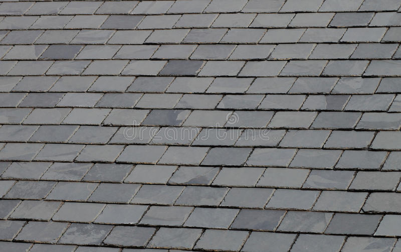 Slate tiled roof. Background of gray or gey slate tiled roof stock image