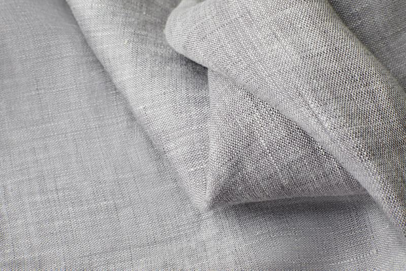 Background of gray-thin linen cloth curled up by a soft wave. selective focus on the upper layer, the lower layer is stock images