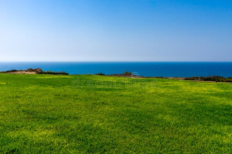 Background green lawn, sea, sky. Background green lawn sea sky. Horizon stock photo