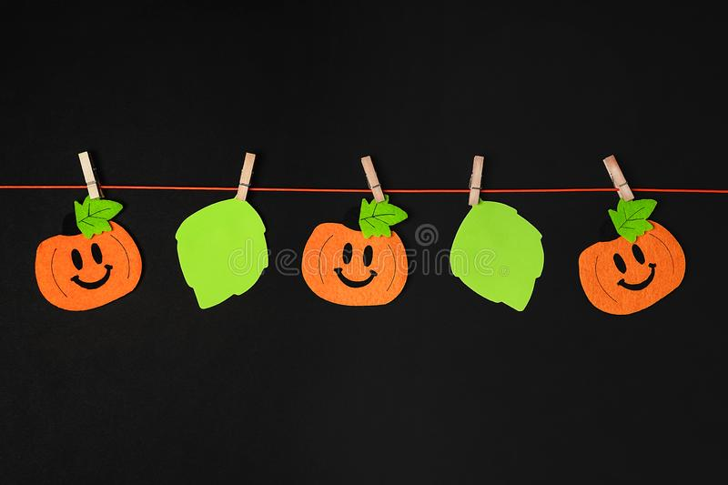 Background of halloween theme decorations. Toy pumpkins hanging on a string with wooden clothespins on black backdrop royalty free stock images