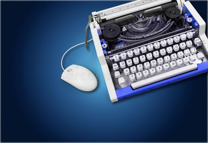 Old typewriter with computer mouse on background stock images
