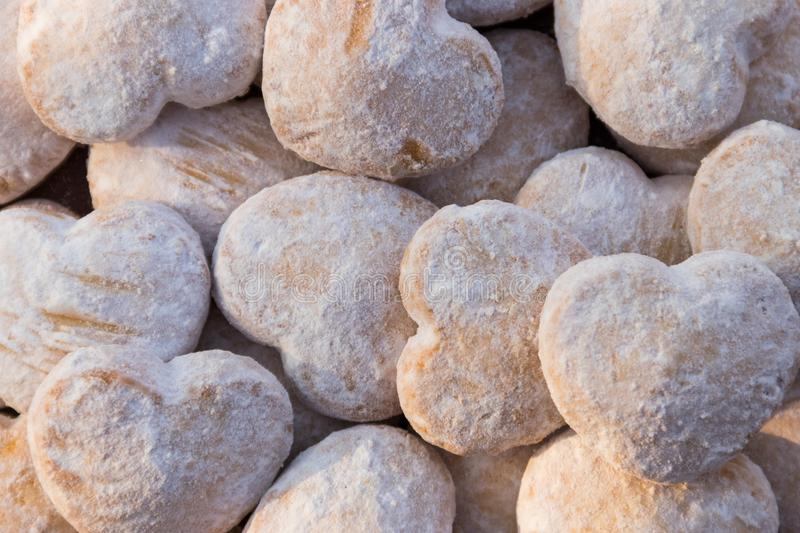 Background of heart shaped cookies covered with powdered sugar. Background of the heart shaped cookies covered with powdered sugar stock images