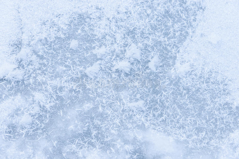 Background ice on the frozen pond with snowflakes abstract form stock images