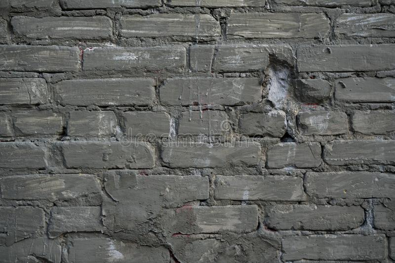 Background image of an abandoned brick wall with painted over paint stock photo