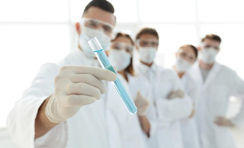Background image is a group of medical workers working with liquids in laboratory stock photo