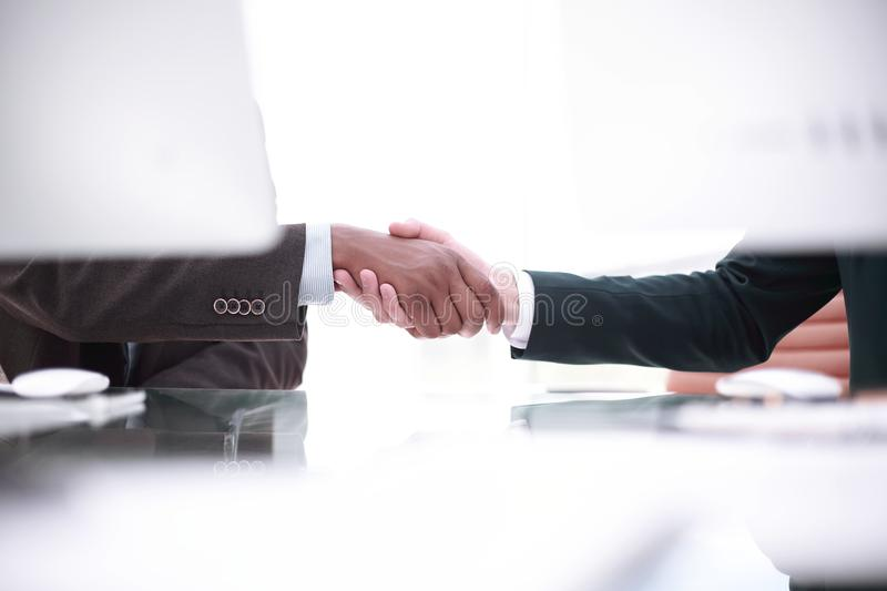 Background image of handshake of business partners above the Desk royalty free stock images