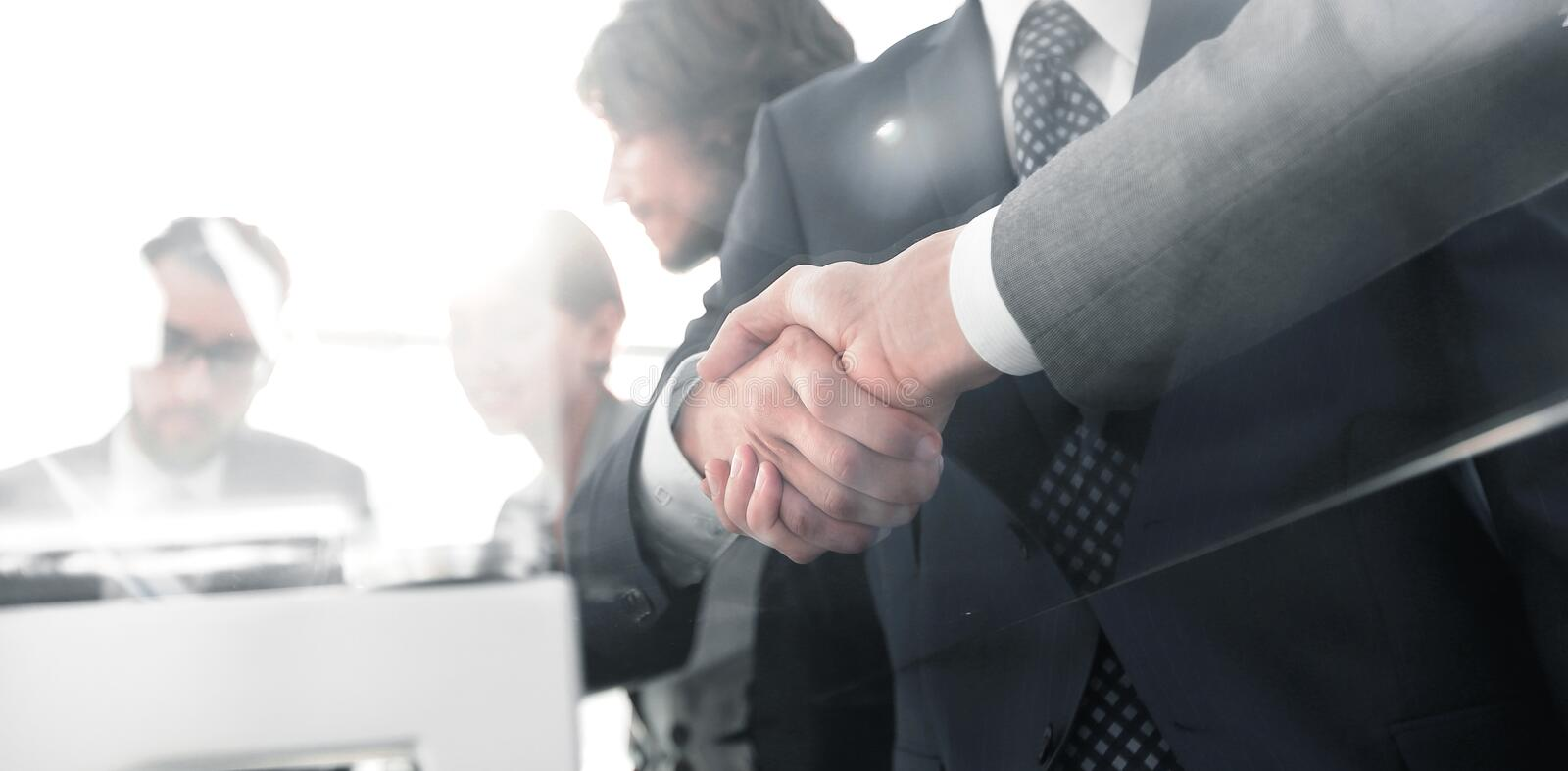 Handshake of business partners in conference room. Background image of handshake of business partners in conference room stock image