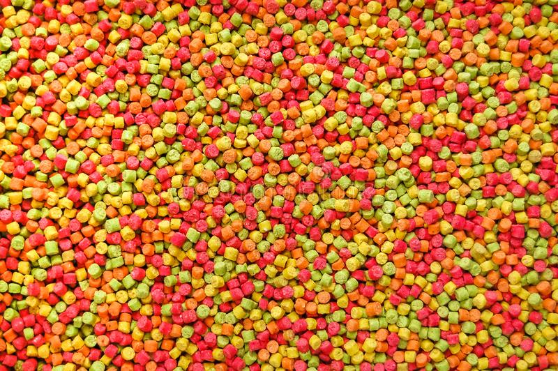 Background image of highly coloured parrot pellets. Overhead. royalty free stock photo