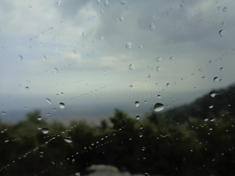 Background image of rain drops on a glass window. Olympia Riviera seen from Olympus on a rainy day,Greece stock images