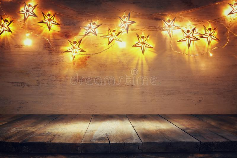 Background image of wooden board table in front of Christmas warm gold garland lights. filtered. selective focus royalty free stock image