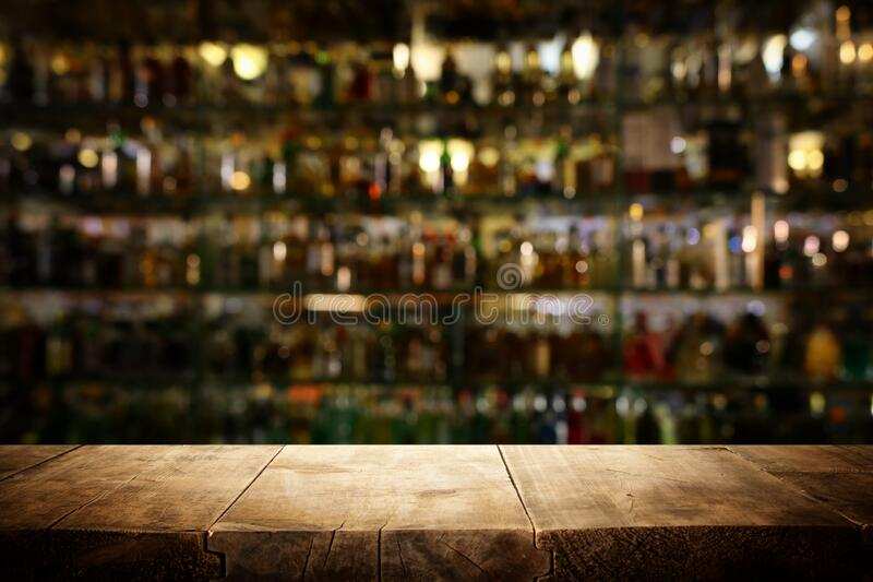 background Image of wooden table in front of abstract blurred restaurant lights stock photos