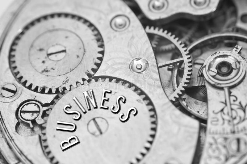 Background with the inscription BUSINESS. Black white background. With metal cogwheels clockwork. Macro. Conceptual photo for your successful business design royalty free stock photo