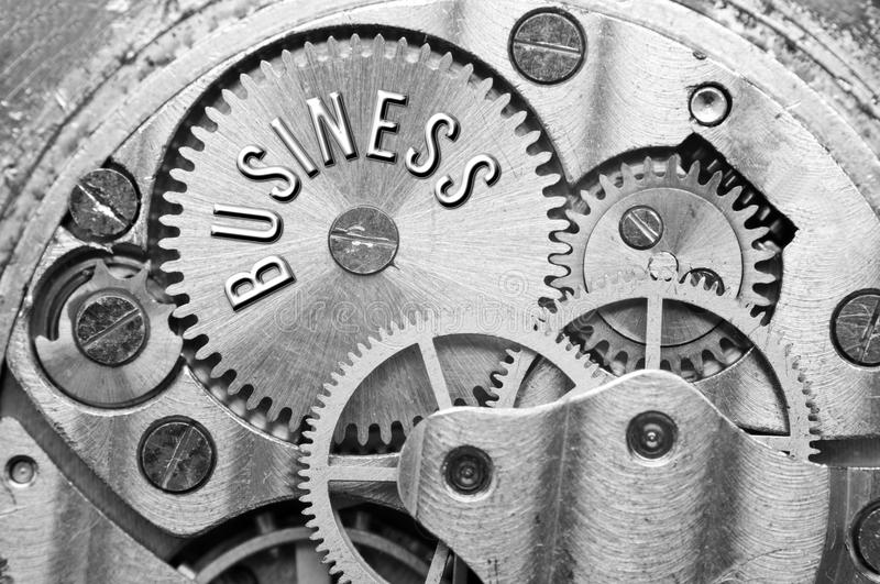 Background with the inscription BUSINESS. Black white background. With metal cogwheels clockwork. Macro. Conceptual photo for your successful business design royalty free stock photography