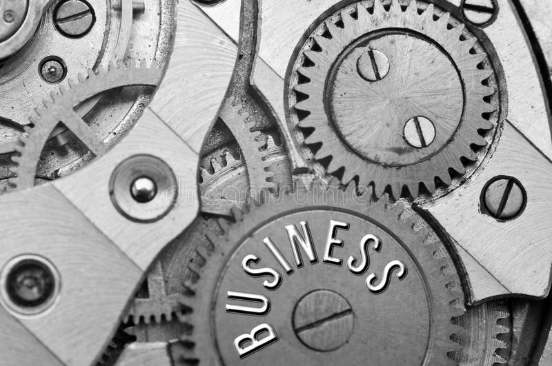 Background with the inscription BUSINESS. Black white background. With metal cogwheels clockwork. Macro. Conceptual photo for your successful business design stock images
