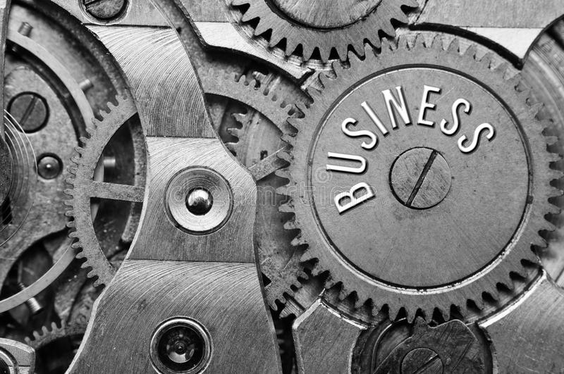 Background with the inscription BUSINESS. Black white background. With metal cogwheels clockwork. Macro. Conceptual photo for your successful business design royalty free stock image