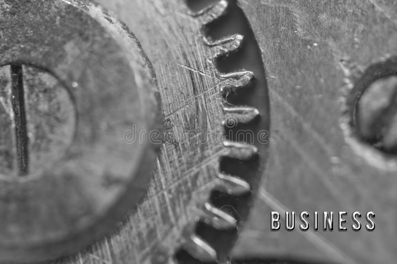 Background with the inscription BUSINESS. Black white background. With metal cogwheels clockwork. Macro. Conceptual photo for your successful business design stock photography