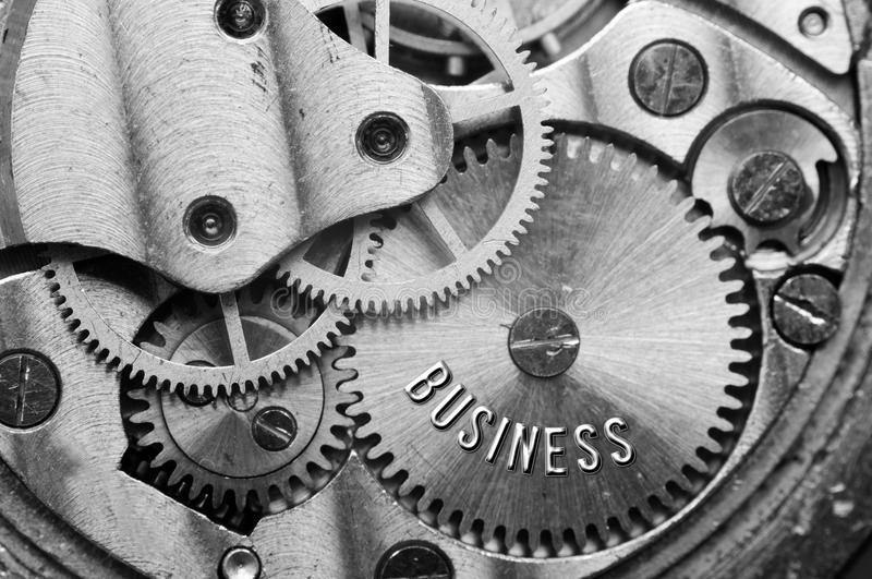 Background with the inscription BUSINESS. Black white background. With metal cogwheels clockwork. Macro. Conceptual photo for your successful business design stock image