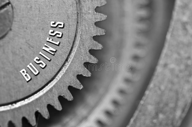 Background with the inscription BUSINESS. Black white background. With metal cogwheels clockwork. Macro. Conceptual photo for your successful business design stock photos