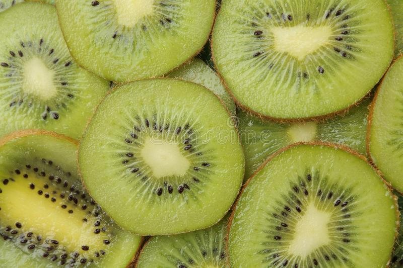Background of kiwi fruit. A lot of ripe kiwi fruit slices. close-up. view from above royalty free stock image