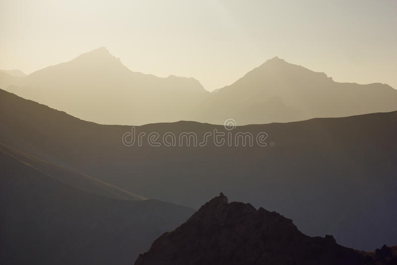 Background layered mountains at sunset. Background layered mountain peaks at sunset stock image
