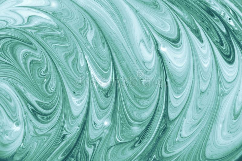 Background with liquid acrylic paint. Pattern of mixed white and aquamarine paint stock image
