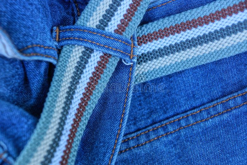 Long striped belt on blue jeans fabric stock photos