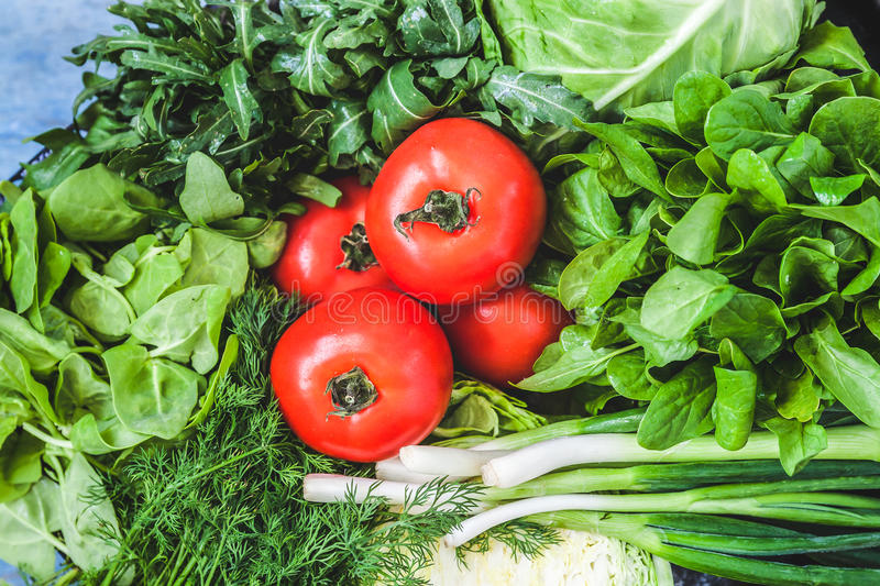 Background of a lot of fresh green different vegetables, herbs a. Nd red tomatoes, top view, close-up. The concept of healthy, proper nutrition, diet, detox stock photography