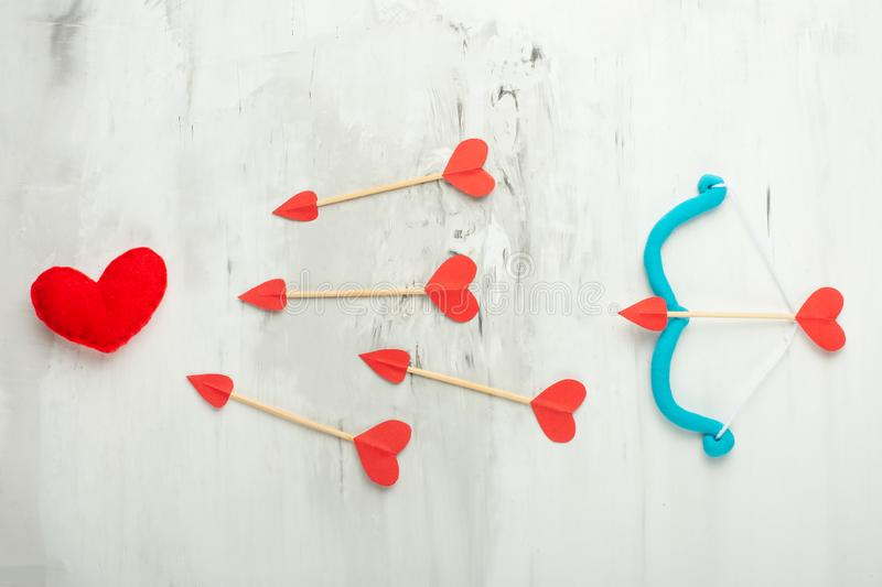 Background of lovers, arrows and cupid bow on a light background. Valentine`s Day. Flat-lay, top view stock photos