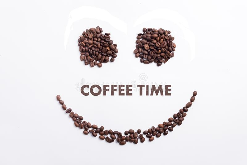 Background made of coffee beans in a smiley face shape with message `Coffee time`. Coffee business advertisement and background stock image
