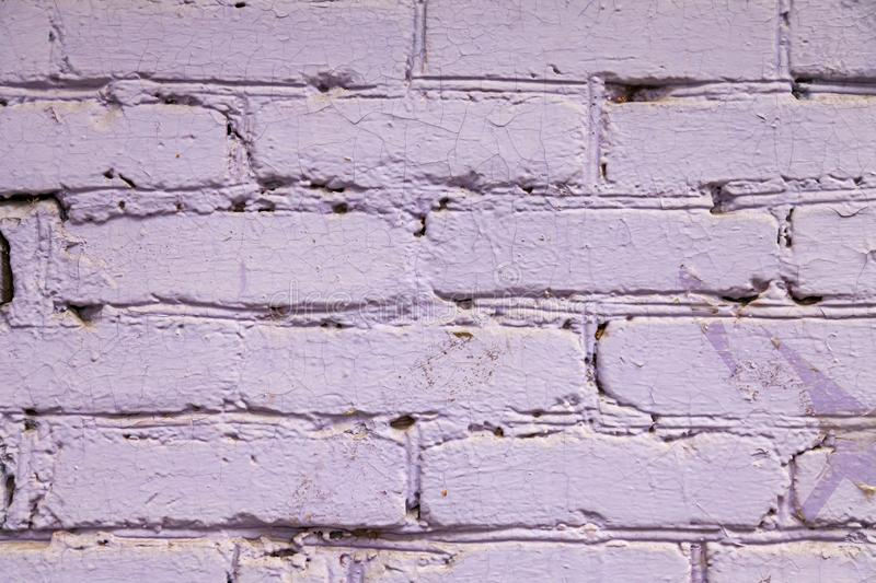 The background is made of purple and pink bricks with a wavy relief, cracks, holes and ditches. Building material for decoration stock image