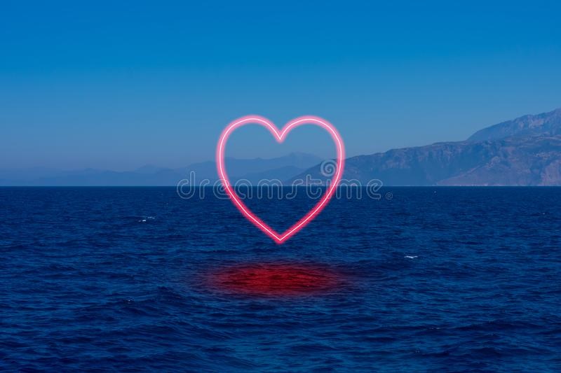 Background made of seascape with mountais in mist and burning heart symbolizing falling in love with ocean royalty free stock photo