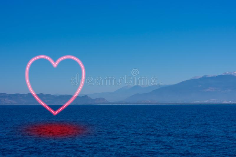 Background made of seascape with mountais in mist. And burning heart symbolizing falling in love with ocean, tourism and boat walks royalty free stock photo