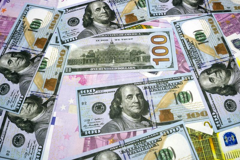 The background of the many currencies the Euro EUR with 500, 200, 100 dollars and euros banknotes. A lot of money. The Euro. The background of the many royalty free stock photos