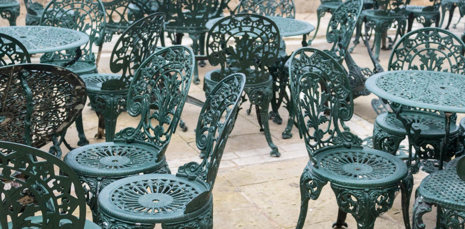 Full size view on many crested and figured metal chairs and tables. Green-blue color royalty free stock image