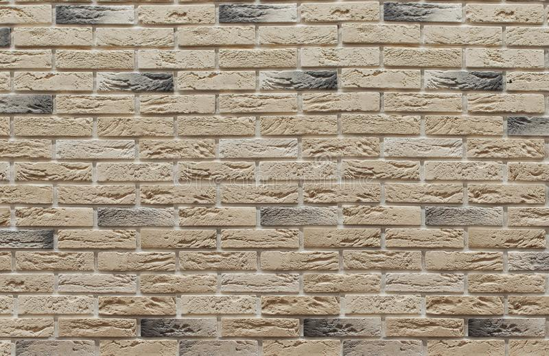Background of masonry brown and beige clinker bricks on the wall, which are used in the repair of premises. Background of masonry colored clinker bricks on the royalty free stock photography