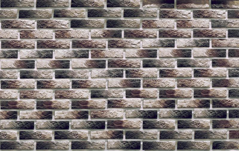 Background of masonry dark clinker bricks on the wall, which are used in the repair of premises. Background of masonry dark colored clinker bricks on the wall stock image