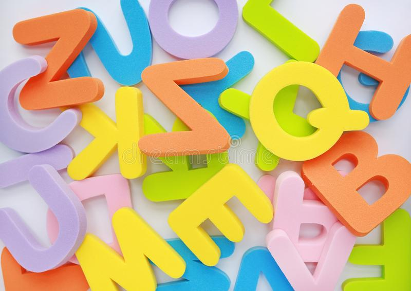 Background messy heap of sponge rubber alphabet letters and numbers.  royalty free stock photography