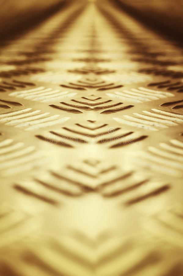 Background of metal with a repeating pattern of bronze color. Close-up, selective focus. Background of metal with a repeating pattern of bronze color. Closeup royalty free stock image