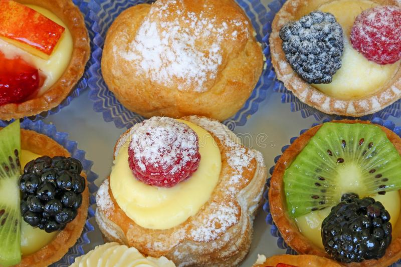 Background of mignon pastries stuffed with creams and fruit. On the tray of a renowned pastry royalty free stock photo
