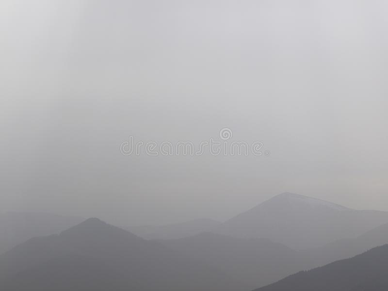 Background misty morning on the mountains horizon. Foggy gentle contours of forested hills in the distance after rain. stock photo