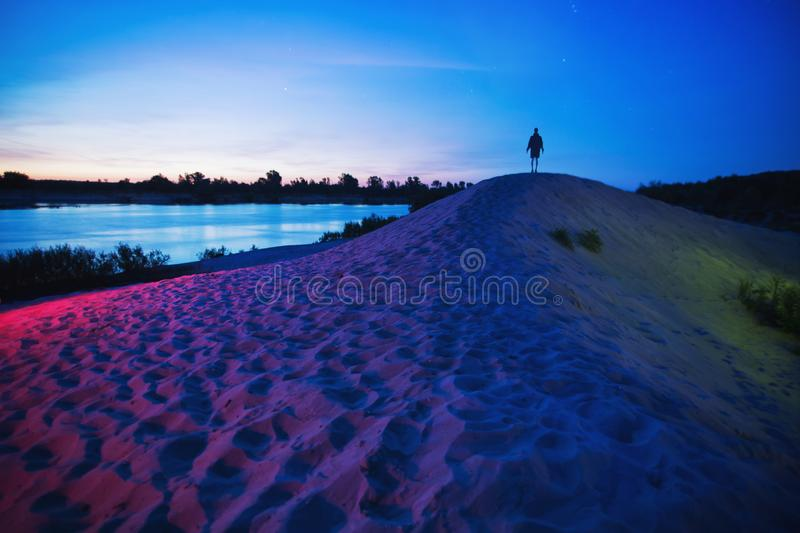 Background of morning sky. Silhouette of man in darkness. Long exposure. Mystical dawn. Dark morning landscape. Colored light on stock image