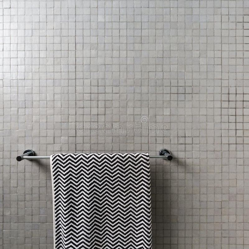 Background of mosaic square wall tiles with chevron towel. On chrome towel rail royalty free stock images