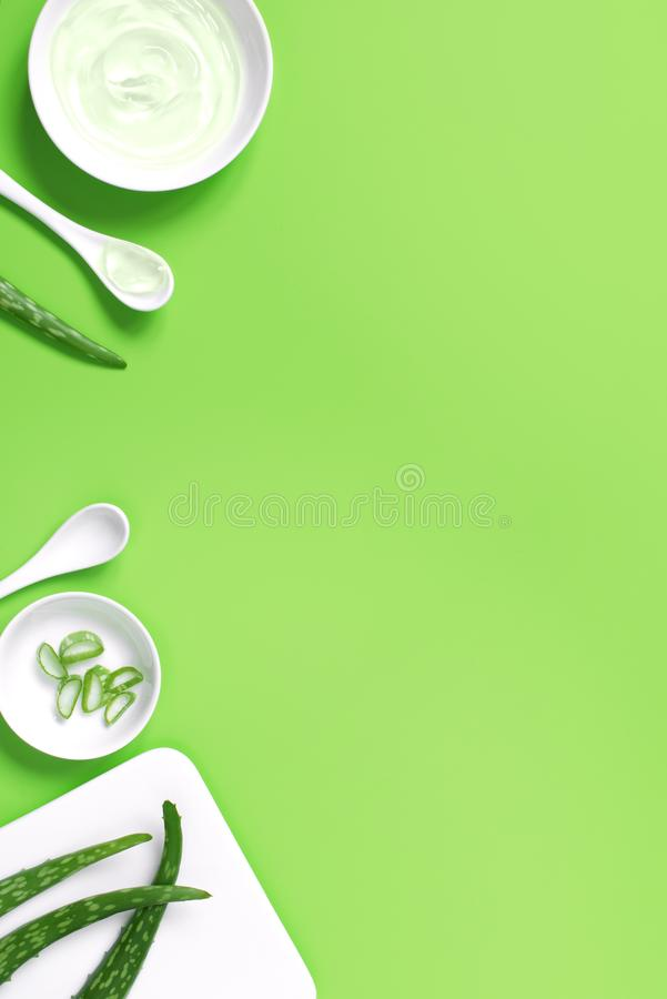 Background with natural cosmetics of aloe vera juice, fresh leaves of aloe. On bright green, copy space stock photography