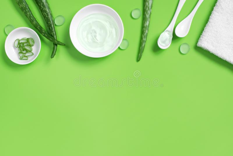 Background with natural cosmetics of aloe vera juice, fresh leaves of aloe. On bright green, copy space stock images