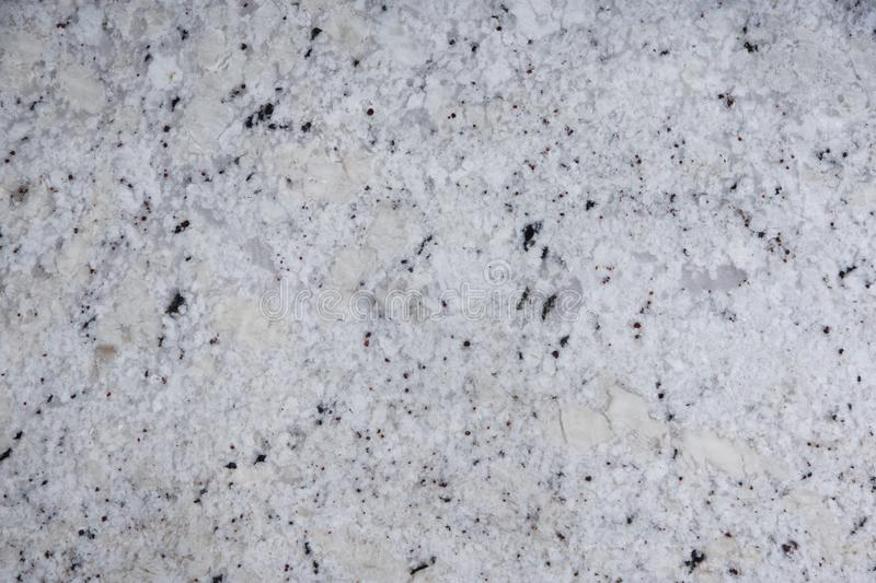 Background natural stone of white color with dark specks, called granite Fantastic White royalty free stock image