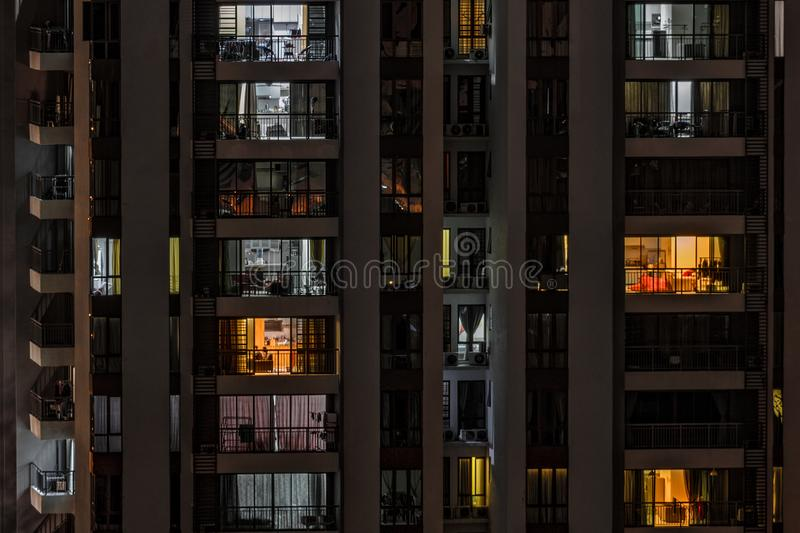 Background with night life in big city. Front view of modern high-rise building with windows of cozy apartments in which light shines and people doing routine royalty free stock photo