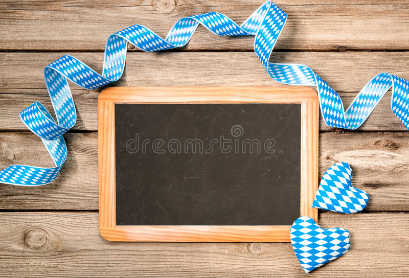 Background for Oktoberfest. Background with empty board, Bavarian ribbon and hearts, Oktoberfest stock photo